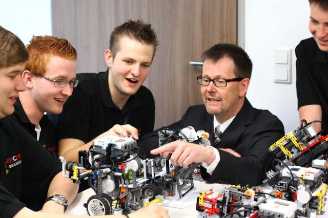 Mendens Bürgermeister Volker Fleige ließ sich bei einem Besuch des Walburgisgymnasiums während der World Robot Olympiad vom WM-Team um Markus Fleige und Kristoph Mattner die Geheimnisse der Roboter-Technik erklären. (Foto: TECHNIK BEGEISTERT)