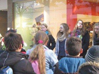 Vor einem Schuhhaus im Zentrum Mendens: Die Schülerinnen der 7b erzählen den Grundschülern, was hier zur Zeit des Nationalsozialismus geschah. (Foto: WBG/Mertens)