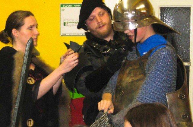 Studierende der Universität Dortmund helfen beim Anlegen der Ritterrüstung, (Foto: WBG/Mertens)