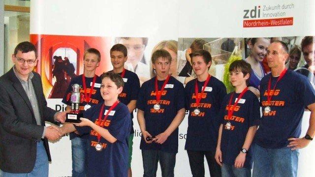 Erster Platz und Pokal für das Walburgisgymnasium: Roboterteam Attraktivundpreiswert_Junior1 mit Herrn Peters (re.) bei der Siegerehrung am 14. Juni 2013 in Meschede. (Foto: WBG/Peters)